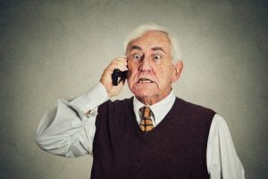 38602457 - angry senior man talking on mobile phone isolated on gray wall background. negative emotions
